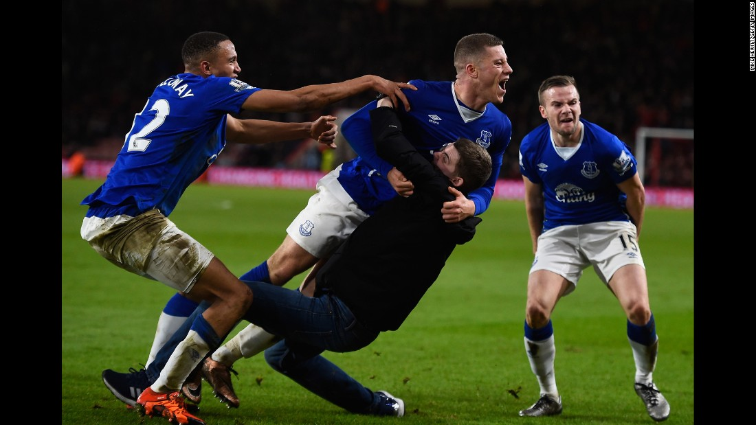 Everton's Ross Barkley is congratulated by a fan who ran onto the field during a Premier League match in Bournemouth, England, on Saturday, November 28. Barkley's late goal appeared to have won Everton the match against Bournemouth, but Junior Stanislas tied the score in the match's dying moments.