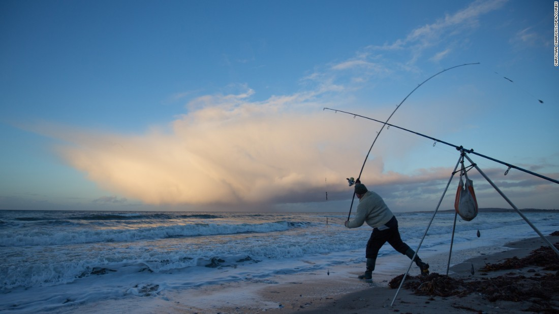 An angler casts his reel during a fishing competition near Weissenhaeuser Strand, Germany, on Saturday, November 28.