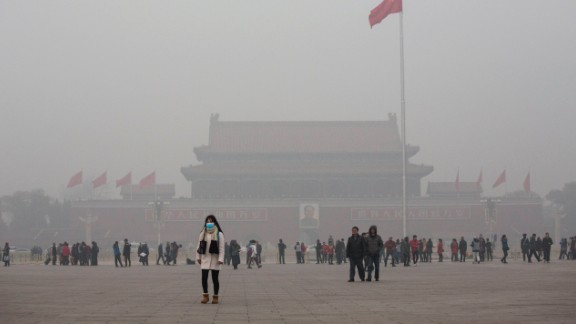 A Chinese woman protects herself with a mask as she walks past Tiananmen Square in smog-hit Beijing on November 30, 2015. Levels of PM 2.5, considered the most hazardous pollutant, crossed 600 units in Beijing, nearly 25 times the acceptable standard set by the World Health Organization.