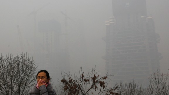 A woman protects herself from pollutants with a piece of cloth as she walks past a construction site on November 30 in Beijing.