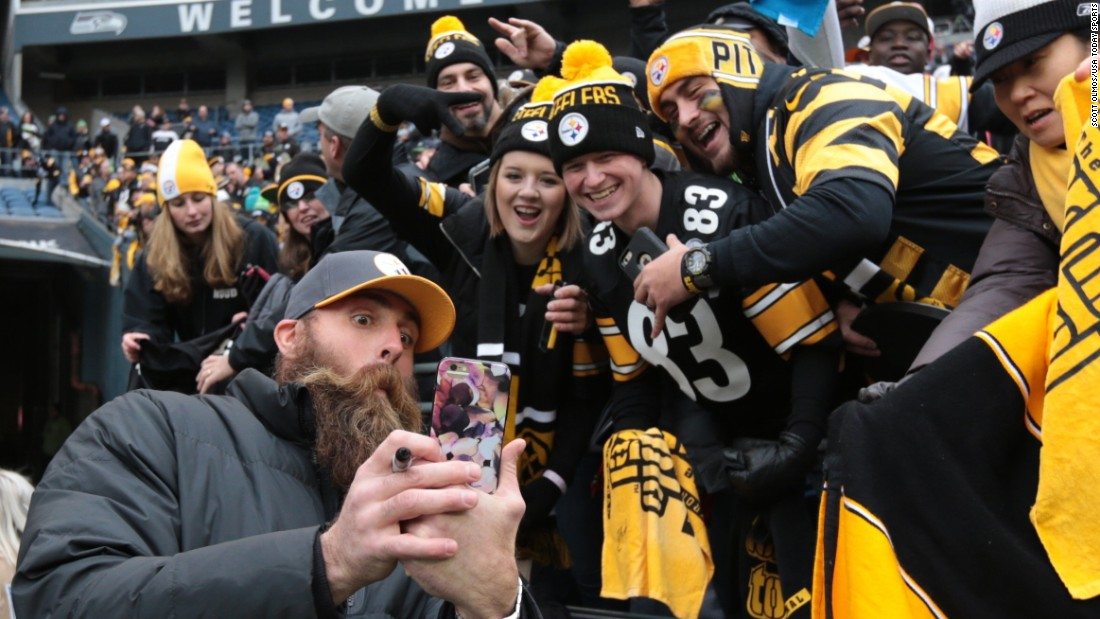 Brett Keisel, a former defensive end for the NFL's Pittsburgh Steelers, takes a selfie with Steelers fans before a game in Seattle on Sunday, November 29.