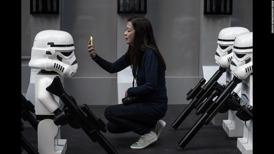 "A woman takes a selfie in front of Lego ""Star Wars"" figures outside a shopping mall in Hong Kong on Monday, November 30."
