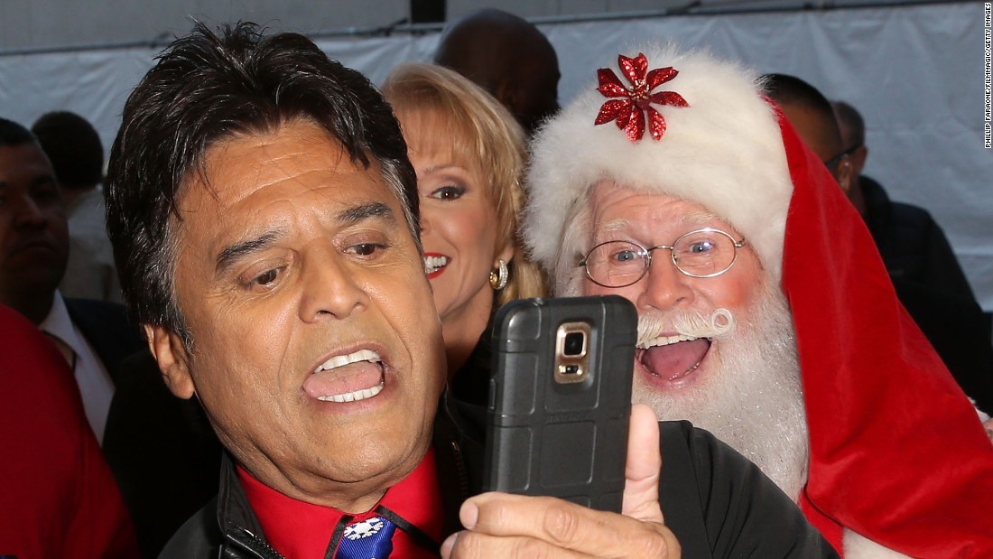 Actor Erik Estrada gets a photo with Santa Claus and television personality Laura McKenzie at the Hollywood Christmas Parade on Sunday, November 29.