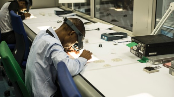 An employee inspects rough diamonds at De Beers' Global Sightholder Sales facility in Gaborone, the largest inspection and valuation operation in the world.