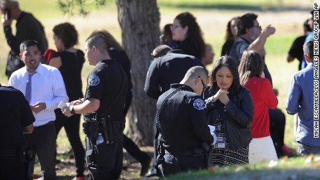 People gather at San Bernardino Golf Course after being evacuated from the scene after the shooting.