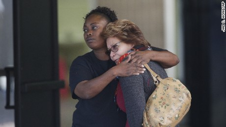 Two women embrace at a community center where family members were gathering to pick up survivors.