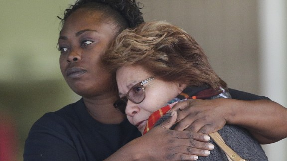 Two women embrace at a community center where family members were gathering to pick up people from the scene.