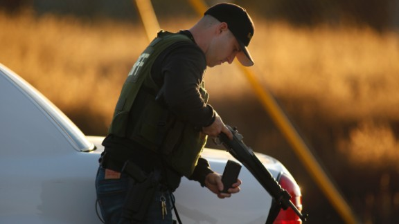 A police officer loads his weapon while pursuing suspects.