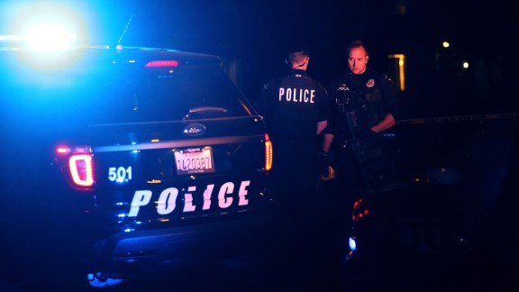 Police officers stand guard as they investigate a suspicious vehicle in Redlands, California, on Wednesday, December 2, after a mass shooting in nearby San Bernardino in which 14 people died and 21 were injured. The shooting took place at the Inland Regional Center, where employees with the county health department were attending a holiday event. The two shooters -- Syed Rizwan Farook and his wife, Tashfeen Malik -- were fatally shot in a gun battle with police hours after the initial incident. Farook worked for the county health department.