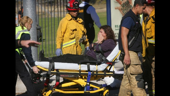 A woman is wheeled away on a stretcher.