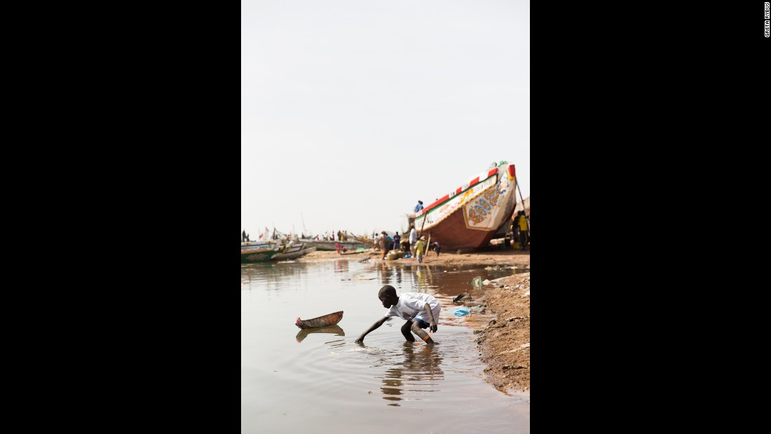 "A young boy plays with a homemade toy boat. Like many boys in Guet Ndar, he began playing with boats as a child and will begin fishing before his childhood is over. ""I was 9 when I began fishing,"" said fishing boat captain Baye Sarr. ""Back then, Guet Ndar was different. According to the scientists, the sea level rises, but here we have a specific situation: every year, there is a period during which the sea rises and comes closer to the housing area. That time is called 'Lock.' Following the end of that period, the sea withdraws back and people call that time 'Ndey.' """