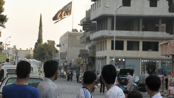 Men look at a large black jihadist flag in Raqqa on September 28, 2013. In Raqqa today, school is banned -- and even small pleasures, like chocolate, are an unaffordable luxury because many cannot work.