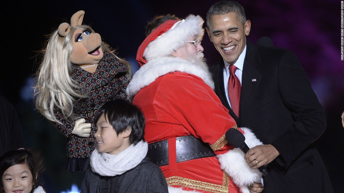 Miss Piggy, Santa Claus and Obama laugh on stage.