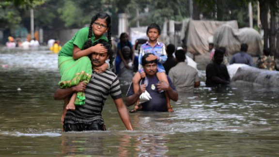 Indian residents carry children as they walk through flood waters in Chennai on December 3.