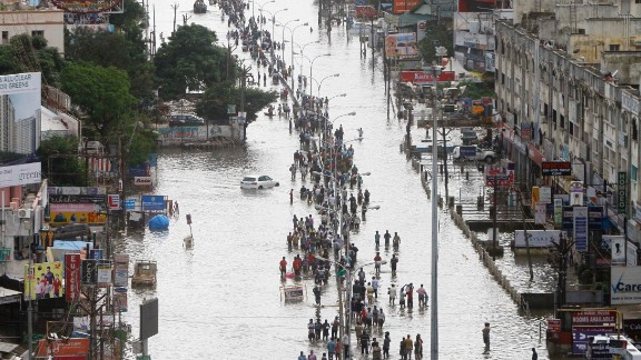 People walk through a flooded street in Chennai, India, Thursday, December 3, 2015. Heaviest rainfalls in more than 100 years have devastated swathes of the southern Indian state of Tamil Nadu, with thousands forced to leave their submerged homes and schools, offices.