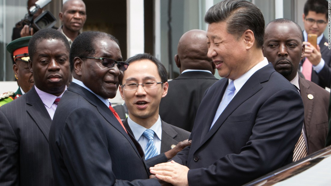 China's President Xi Jinping (2nd R) shakes  hands  with Zimbabwe's President Robert Mugabe (2nd L) as he arrive on December 1, 2015 in Harare. China's President Xi Jinping visited Zimbabwe on December 1 on a rare trip by a world leader to a country shunned by Western powers over President Robert Mugabe's widely-criticised record on human rights. The two leaders held talks and oversaw the signing by their ministers of 10 agreements and memorandums of understanding covering energy, aviation, telecommunications and investment promotion deals to shore up Zimbabwe's economy, which has fallen into dire straits under Mugabe's rule.