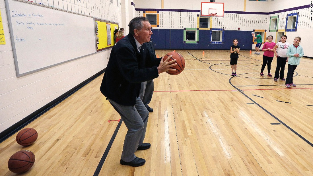 Republican presidential candidate and Ohio Gov. John Kasich takes a shot on the basketball court at the Fisk Middle School prior to a campaign stop in Salem, New Hampshire, on Thursday, December 3.