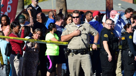A crowd gathers behind police lines near the scene of a shooting on December 2, 2015, in San Bernardino, California. One or more gunman opened fire inside a building with reports of 20 victims at a center that provides services for the disabled. Police were still hunting for the shooter, saying one to three possible suspects were involved. Heavily armed SWAT teams, firefighters and ambulances swarmed the scene, located about an hour east of Los Angeles, as police warned residents away. (Photo: FREDERIC J. BROWN/AFP/Getty Images)