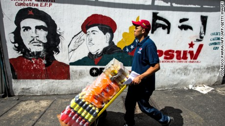A worker passes propaganda graffiti in Caracas ahead of the vote.