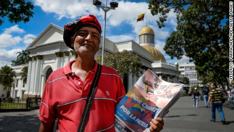"A news vendor holds electoral propaganda outside National Asembly, in Caracas on December 4, 2015. For the first time in 16 years of ""Bolivarian revolution"" under late president Hugo Chavez and his successor Nicolas Maduro, polls show their rivals could now win a majority in the National Assembly.  AFP PHOTO/FEDERICO PARRA / AFP / FEDERICO PARRA        (Photo credit should read FEDERICO PARRA/AFP/Getty Images)"