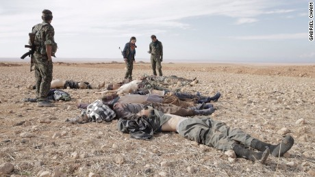 After battle, Kurdish fighters -- women among them -- secure the area after checking dead ISIS fighters for suicide vests.