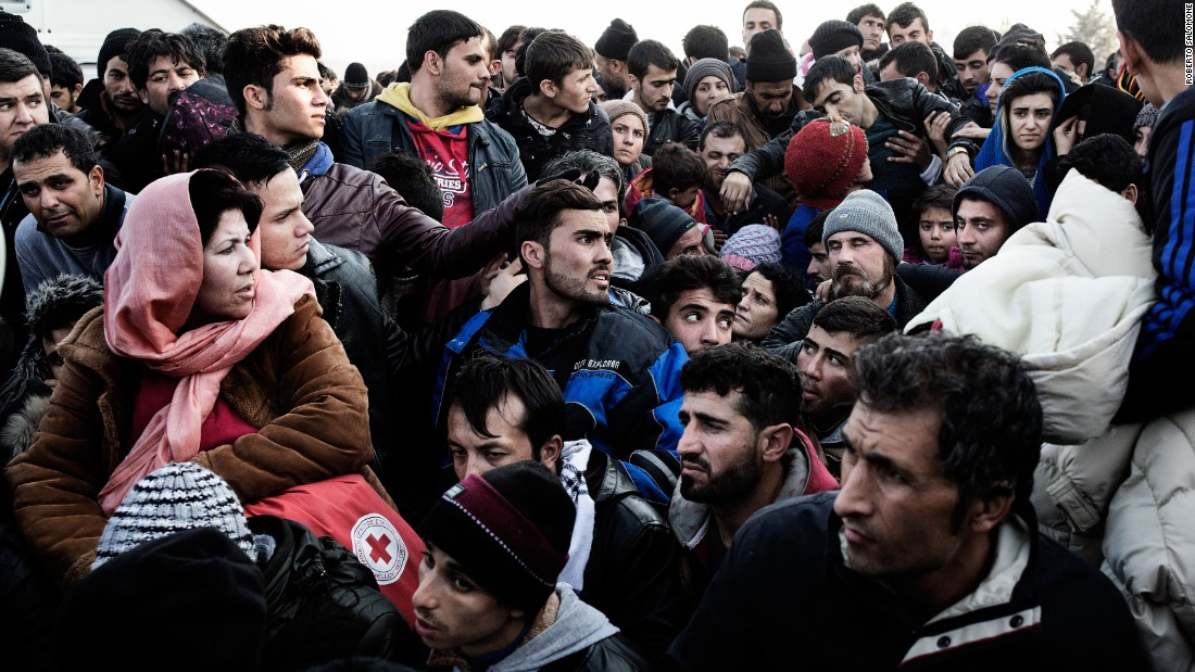 Migrants waiting to enter Macedonia stand at the border between Greece and Macedonia near the town of Idomeni, Greece, on Saturday, December 5.