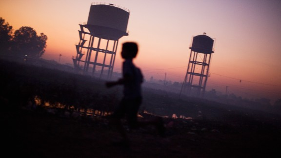 BHOPAL, INDIA - NOVEMBER 27:  A children plays near water towers in front of their homes near the Union Carbide factory on November 27, 2009 in Bhopal, India. Twenty-five years after an explosion causing a mass gas leak, in the Union Carbide factory in Bhopal, killed at least eight thousand people, toxic material from the biggest industrial disaster in history continues to affect Bhopalis. A new generation is growing up sick, disabled and struggling for justice. The effects of the disaster on the health of generations to come, both through genetics, transferred from gas victims to their children and through the ongoing severe contamination, caused by the Union Carbide factory, has only started to develop visible forms recently.  Annan suffers from cerebral palsy and receives vital rehabilitative support and care at the Chingari Trust Rehabilitation Clinic.  (Photo by Daniel Berehulak/Getty Images)