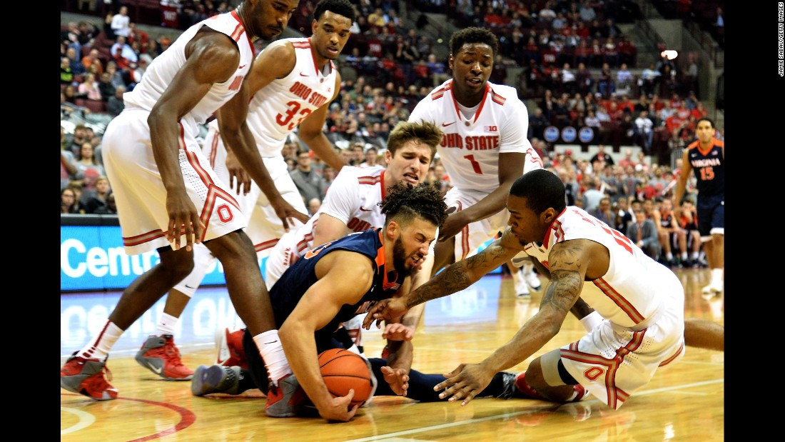 Virginia's Anthony Gill is surrounded by Ohio State players as they battle for a loose ball Tuesday, December 1, in Columbus, Ohio.