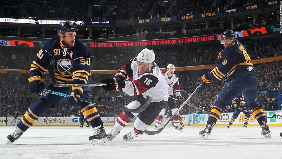 Arizona's Max Domi, center, competes against Buffalo's Ryan O'Reilly during an NHL game in Buffalo, New York, on Friday, December 4.