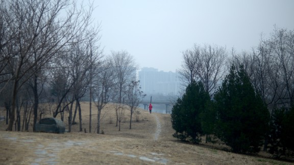 A woman walks along a path at a park in Beijing on December 7. Smog is blurring the view of the buildings in the background.