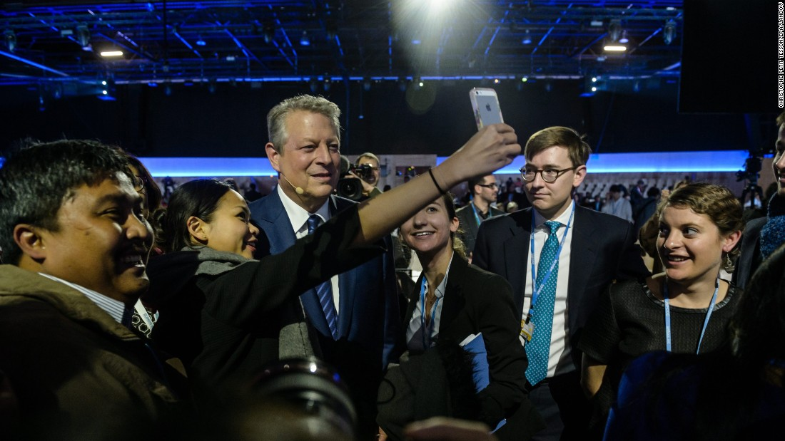 Former U.S. Vice President Al Gore stops for a selfie before giving a speech at COP21, a climate change conference in Le Bourget, France, on Saturday, December 5.