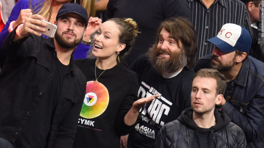 A fan takes a selfie with actors Olivia Wilde, Will Forte and Jason Sudeikis at a Los Angeles Clippers game on Saturday, December 5.