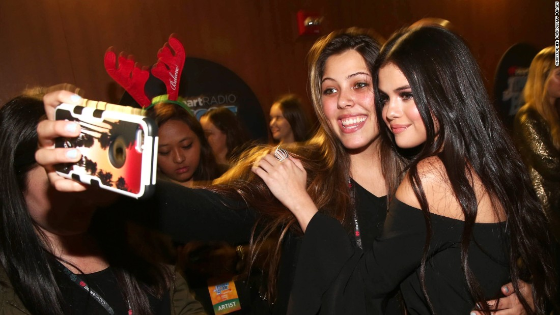 Singer Selena Gomez poses for a fan's selfie at a Jingle Ball concert in Los Angeles on Friday, December 4.