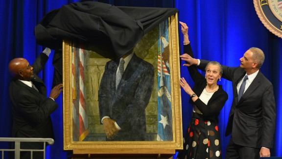 A drape gets momentarily stuck as U.S. Attorney General Eric Holder and his wife, Sharon, help artist Simmie Knox unveil Holder