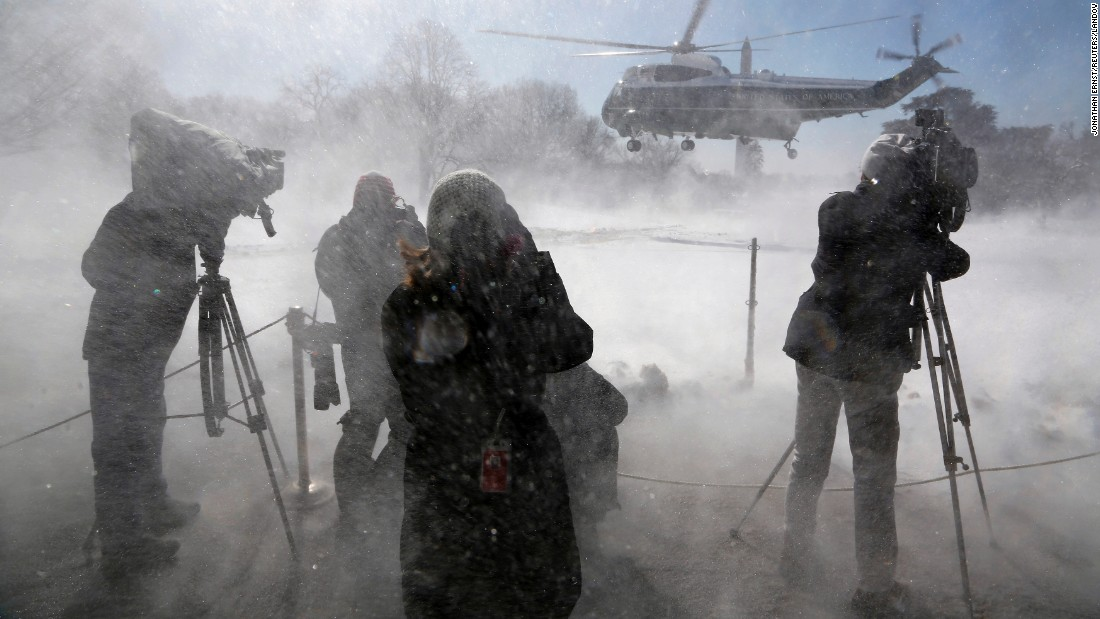 Reporters are hit by snow as President Obama leaves the White House on Marine One on Friday, March 6.