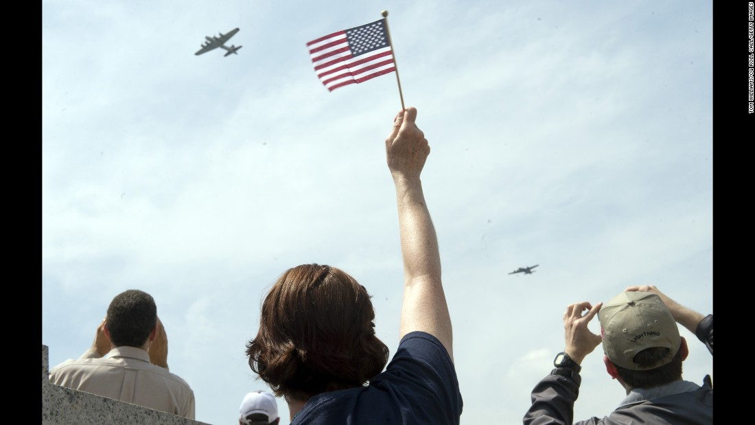 A spectator waves to World War II-era aircraft as they fly over the National World War II Memorial in Washington on Friday, May 8. The flyover commemorated the 70th anniversary of V-E Day.