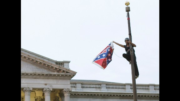 Bree Newsome removes the Confederate battle flag from a monument in front of the South Carolina State House on Saturday, June 27. She was charged with defacing a monument, and a new flag went up within about an hour, according to the South Carolina Department of Public Safety. Not long after she was led away in handcuffs, Newsome became an online hero, a trending topic on social media and the subject of an online fundraiser. South Carolina took down the flag on its own in July, ending a 54-year run on the Capitol grounds.