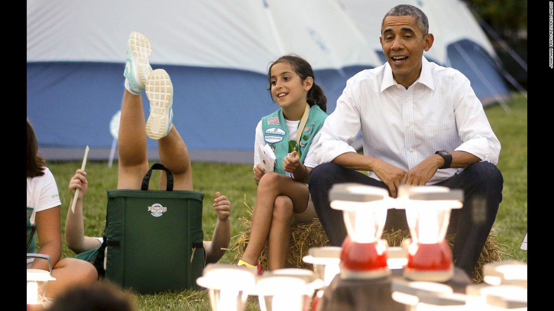 A girl near President Obama loses her balance in her chair as she and other Girl Scouts camped on the South Lawn of the White House on Tuesday, June 30.