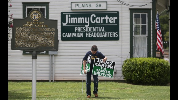 Jill Stuckey places signs in front of Jimmy Carter