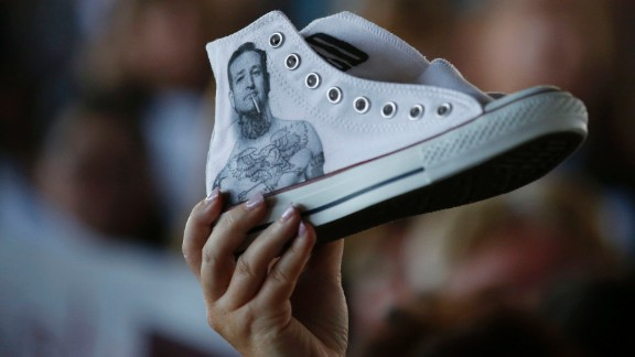 A supporter of Republican presidential candidate Ted Cruz holds up a sneaker with the U.S. senator