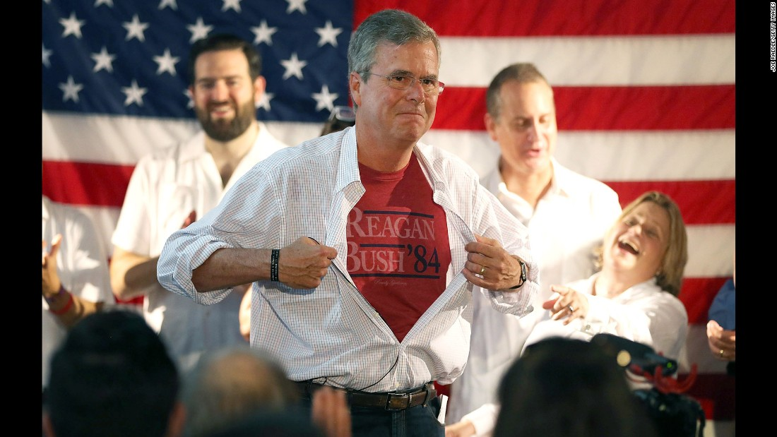 Republican presidential candidate Jeb Bush shows off a Reagan-Bush '84 T-shirt as he speaks during a Miami field office opening on Saturday, September 12.