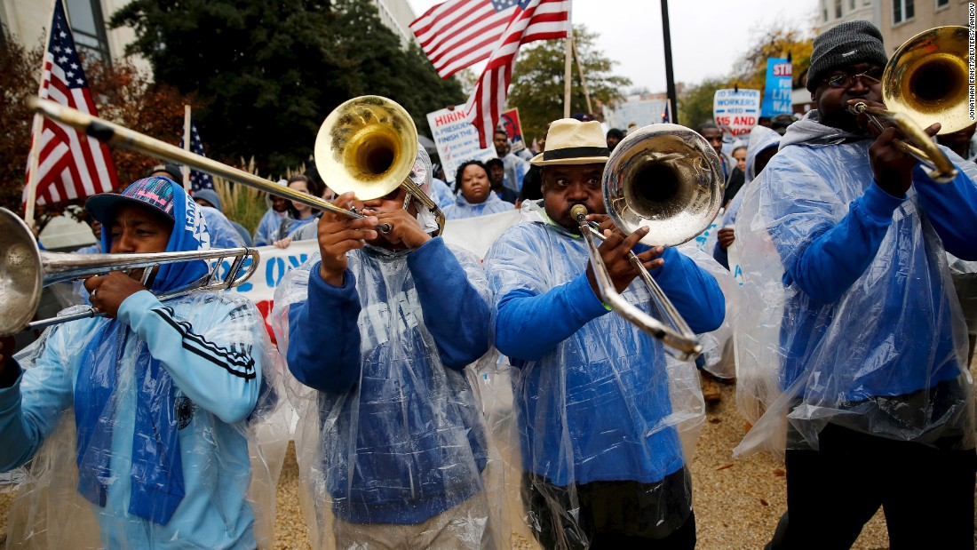 Trombonists lead the way as Senate contract cooks and cleaning workers march for higher wages near the U.S. Capitol on Tuesday, November 10.