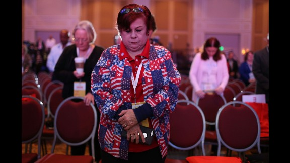 People pray for victims of the Paris terrorist attacks while attending the Sunshine Summit, an event in Orlando hosting Republican presidential candidates, on Saturday, November 14.
