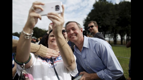 Someone tries to cover up the Bernie Sanders T-shirt on a woman taking a selfie with another Democratic presidential candidate, Martin O