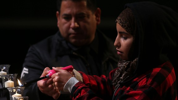 GRANADA HILLS, CA - DECEMBER 05: A Los Angeles police officer helps a mourner light a candle for the victims of the mass shooting in San Bernardino during a United We Stand vigil at Granada Hills Charter High School on December 5, 2015 in Granada Hills, California. The FBI has officially labeled the attack carried out by Syed Farook and his wife Tashfeen Malik as an act of terrorism. The San Bernardino community continues to mourn the attack at the Inland Regional Center in San Bernardino that left at least 14 people dead and another 21 injured. (Photo by Justin Sullivan/Getty Images)
