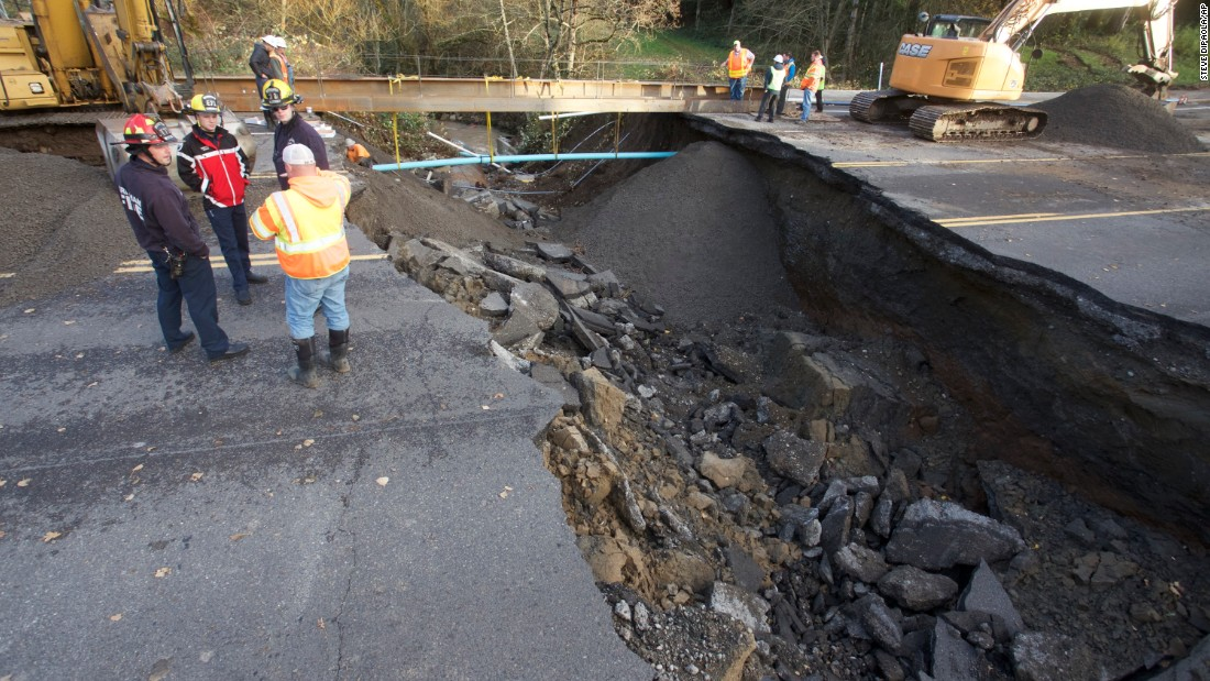 Fire and maintenance personnel look at a large sinkhole in Gresham, Oregon, on December 9.