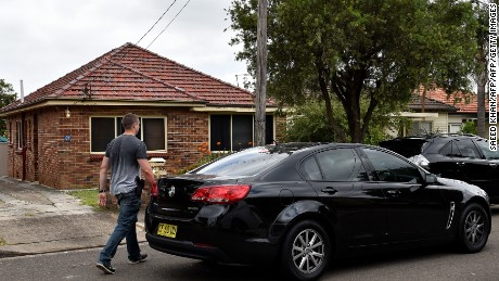 Police officers are seen outside a house in a southwestern suburb of Sydney after conducting a number of raids around the city