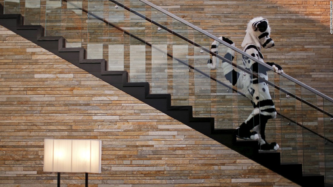 "A person wearing a ""fursuit"" costume walks down the stairs at the Midwest FurFest in Rosemont, Illinois, on Friday, December 4. More than 5,000 people gathered for the convention, where people dress as up as anthropomorphic animals."