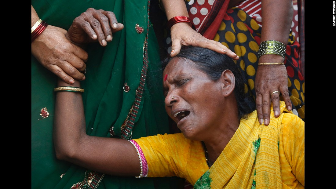 A woman cries after she lost her husband in a fire that broke out in slums in Mumbai, India, on Monday, December 7. Hundreds of homes were reportedly destroyed.