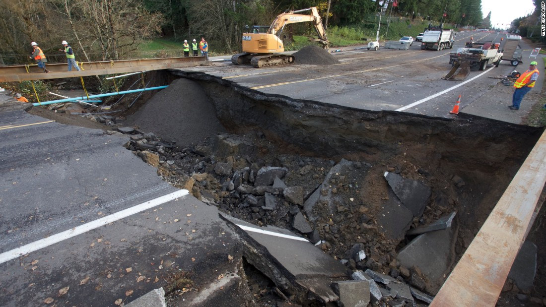 "Maintenance personnel look at a large sinkhole in Gresham, Oregon, on Wednesday, December 9. <a href=""http://www.cnn.com/2015/12/10/us/gallery/northwest-flooding/index.html"" target=""_blank"">Heavy rain and winds</a> have battered Oregon and Washington state, causing widespread flooding and power outages."